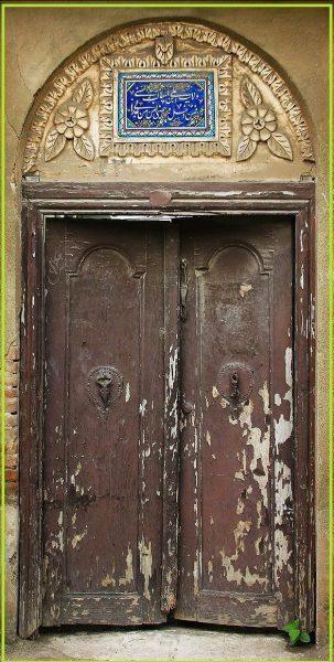 کتیبه فیروزه ای رنگ بالای درب چوبی