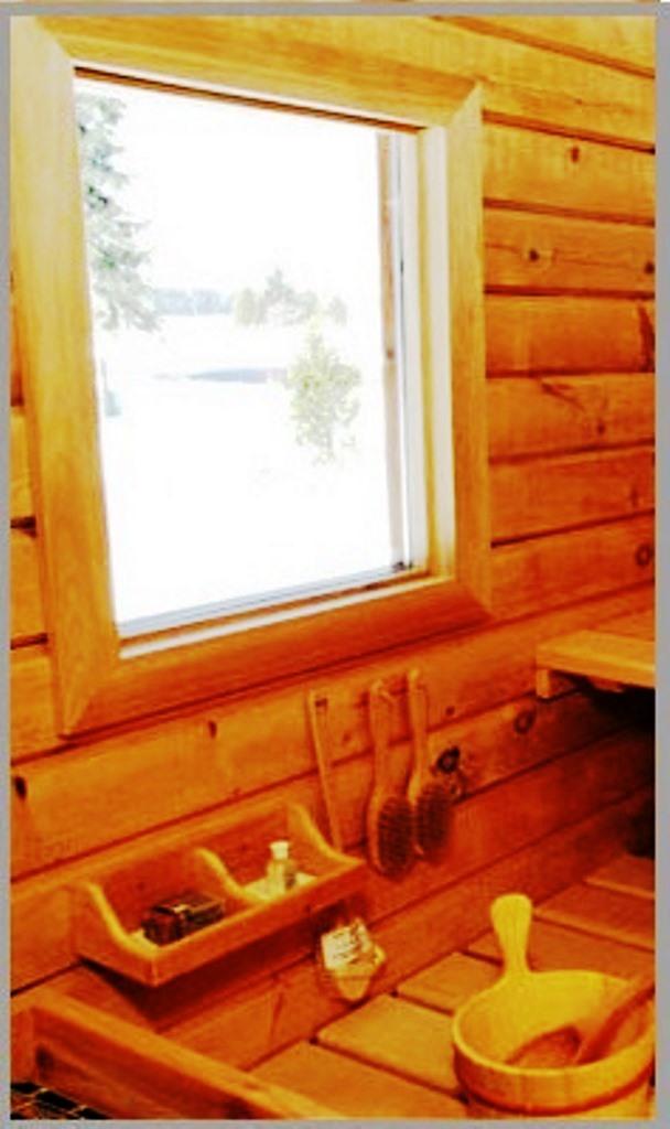 لوازم چوبی و دکوری سونای خشک فنلاندی در کنار پنجره ای چوبی