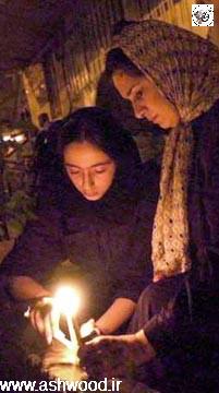 مادر و دختر ایرانی در تهران که در حال روشن کردن شمع به یاد کشتهشدگان حملات ۱۱ سپتامبر هستند.