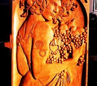 تصویر یک خانم بر روی چوب کنده کاری شده با دستانی پر از میوه انگور