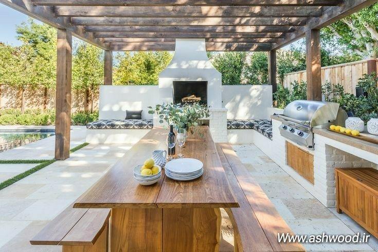 یک آشپزخانه مجهز در فضای باز، پرگولا، کفپوش سنگ و کانتر آشپزخانه آجری
